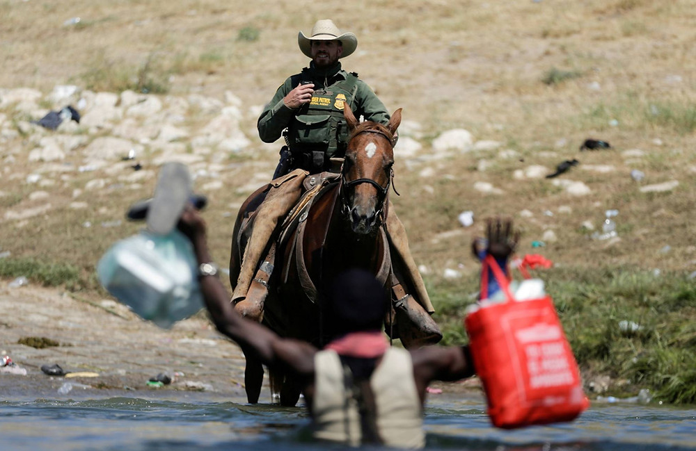 Un oficial de la patrulla fronteriza de Estados Unidos corta el camino a un inmigrante que busca solicitar asilo cuando intenta ingresar al país por el río Grande.