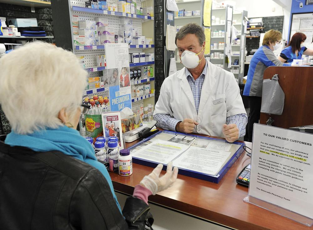 El farmacéutico Karl Oseli ayuda a un cliente en su tienda Glen Cade Pharmacy & Home Health Care.