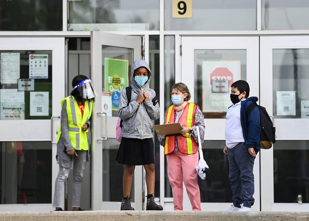 Los niños esperan para ingresar a la Escuela Comunitaria Portage Trail, que es parte de la Junta Escolar del Distrito de Toronto (TDSB) durante la pandemia de COVID-19 en Toronto el martes 15 de septiembre de 2020.