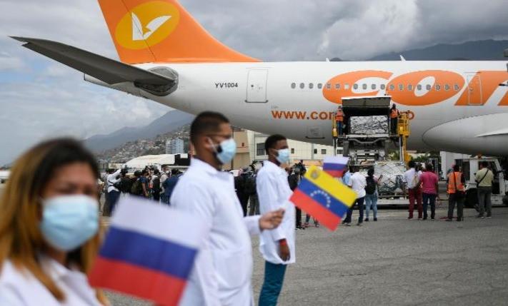 Trabajadores de la salud sostienen banderas nacionales de Venezuela y Rusia mientras descargan un cargamento de la vacuna rusa COVID-19 Sputnik V, en el Aeropuerto Internacional Simón Bolívar en Maiquetía, Venezuela, el sábado 13 de febrero de 2021.