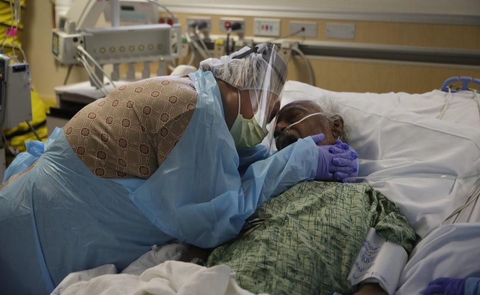 En esta fotografía de archivo del 31 de julio de 2020, Romelia Navarro, de 64 años, llora mientras abraza a su esposo, Antonio, en sus momentos finales en una unidad de COVID-19 en el Centro Médico St. Jude en Fullerton, California. -19 casi ha superado los 500.000, una cifra tan asombrosa que un importante investigador de la salud dice que es difícil imaginar a un estadounidense que no haya perdido a un familiar o que no conozca a alguien que murió.