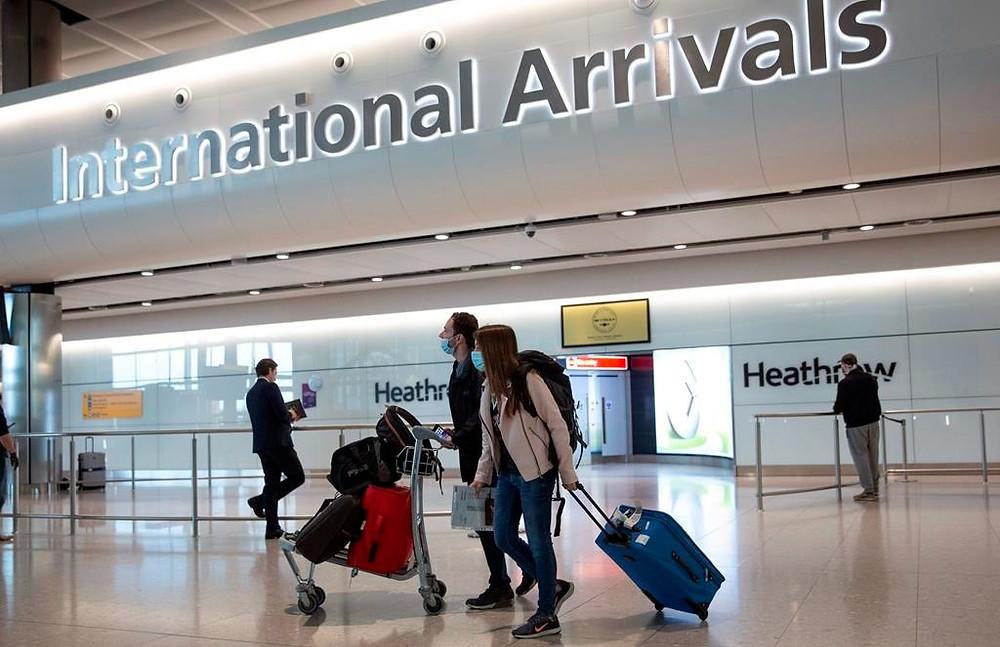 En esta foto de archivo del lunes 8 de junio de 2020, los pasajeros con mascarillas llegan al aeropuerto de Heathrow en Londres.