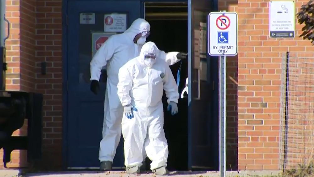 Personal de limpieza en Mason Road Junior Public School después de que se cerró cuando se declaró un brote.