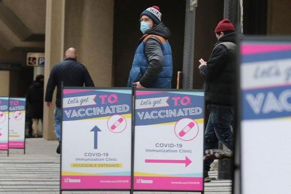 Los trabajadores de primera línea y esenciales esperan en la fila mientras se abre la primera clínica de vacunación COVID-19 de gran volumen en Toronto.