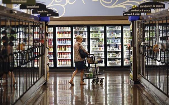 Un cliente empuja un carrito de compras a través del pasillo de alimentos congelados dentro de una tienda de comestibles Kroger Co. en Louisville, Kentucky, EE. UU., El 14 de junio de 2017.