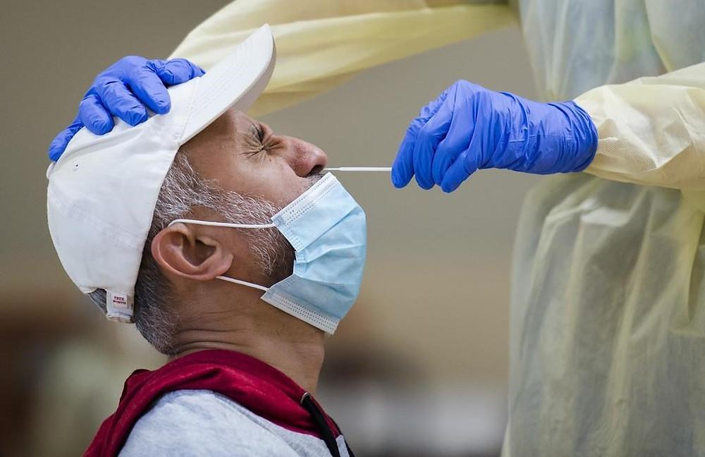 Friaaz Azeez se hace la prueba de COVID-19 de un trabajador de la salud en un centro de pruebas emergente en el Instituto Islámico de Toronto durante la pandemia de COVID-19 en Scarborough, Ontario, el viernes 29 de mayo de 2020.