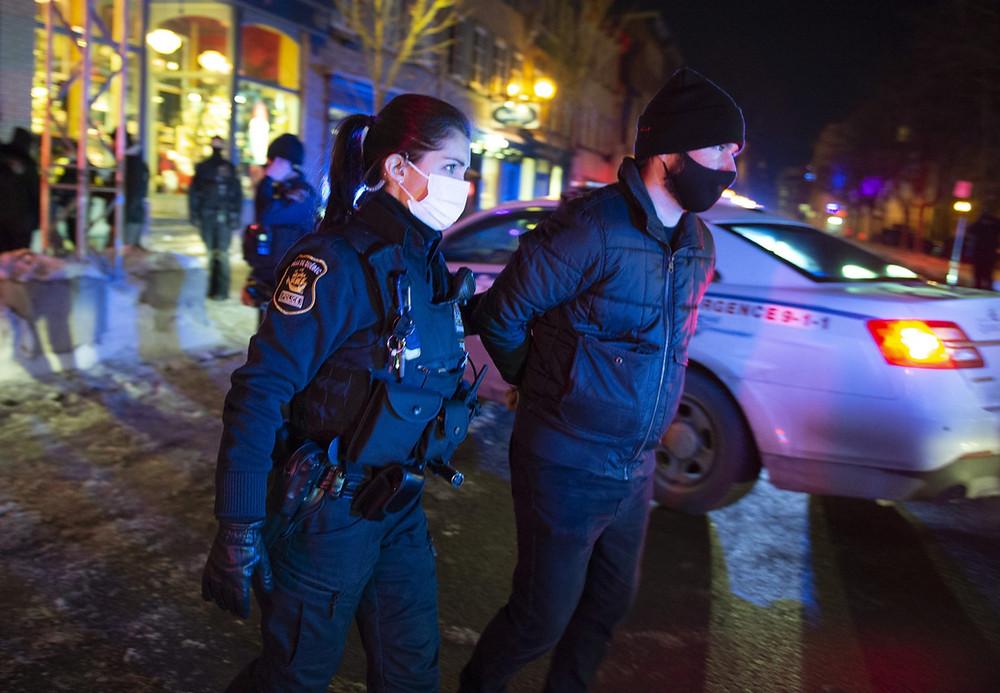 Un hombre es arrestado por la policía después de las 8 pm cuando comienza el toque de queda en la provincia de Quebec para contrarrestar la propagación del COVID-19 el sábado 9 de enero de 2021 en la ciudad de Quebec. Un puñado de manifestantes caminó hacia el centro para protestar por el toque de queda.