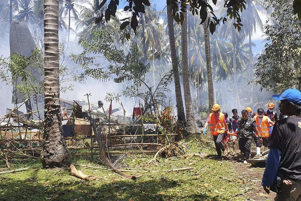 En esta foto publicada por la Fuerza de Tarea Conjunta - Sulu, los rescatistas llevan un cuerpo del lugar donde un avión militar filipino C-130 se estrelló en la ciudad de Patikul, provincia de Sulu, en el sur de Filipinas el domingo 4 de julio de 2021.