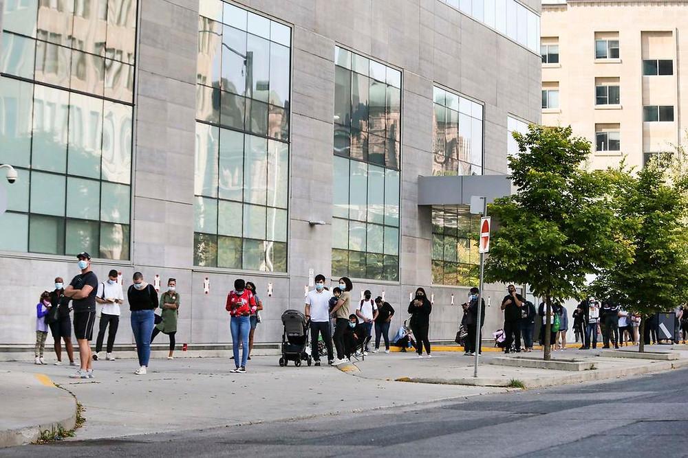 gente espera afuera de un centro de evaluación de COVID-19 en el Women's College Hospital en Grosvenor St. en el centro de Toronto