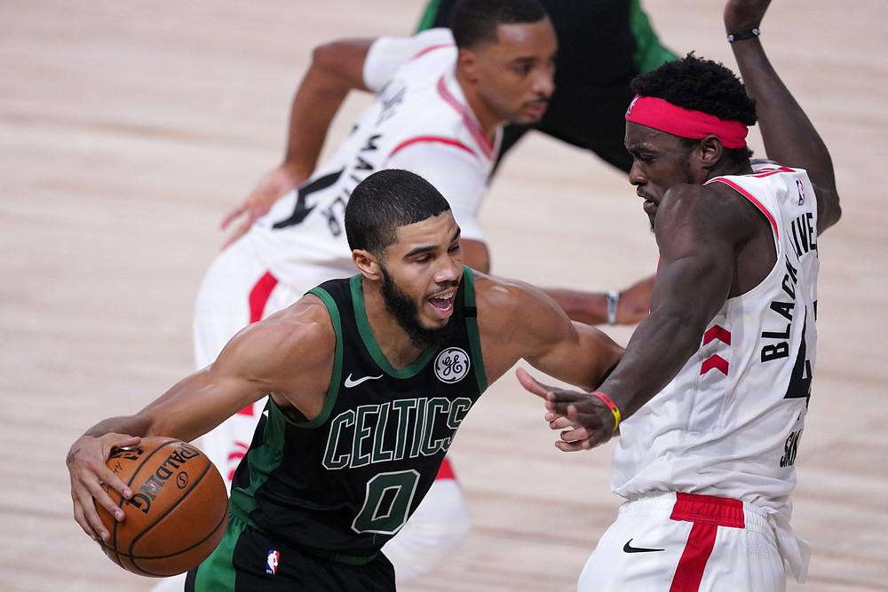 Jayson Tatum (0) de los Celtics de Boston impulsa contra Pascal Siakam de los Raptors de Toronto durante la segunda mitad de un juego de baloncesto de semifinales de la conferencia de la NBA el viernes 11 de septiembre de 2020 en Lake Buena Vista, Florida