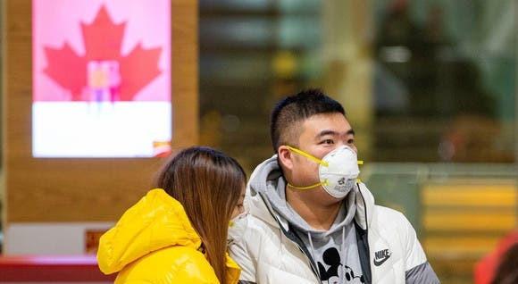 Las personas que esperan a los pasajeros usan máscaras en las llegadas al aeropuerto de Pearson, poco después de que Toronto Public Health recibió la notificación del primer caso presuntamente confirmado de coronavirus en Canadá, en Toronto.