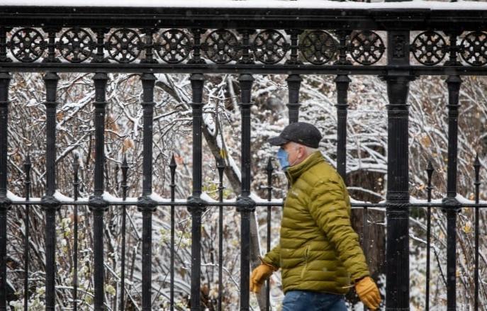 Un hombre con una máscara camina en el centro de Toronto.