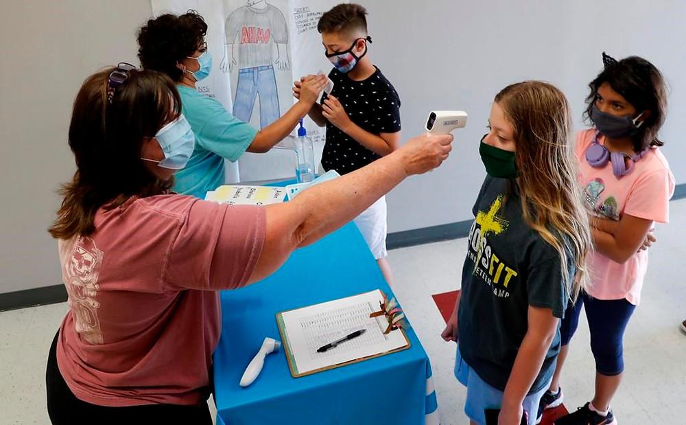 las maestras de ciencias Ann Darby, izquierda, y Rosa Herrera registran a los estudiantes antes de un campamento STEM de verano en la escuela secundaria Wylie el martes 14 de julio de 2020 en Wylie, Texas.
