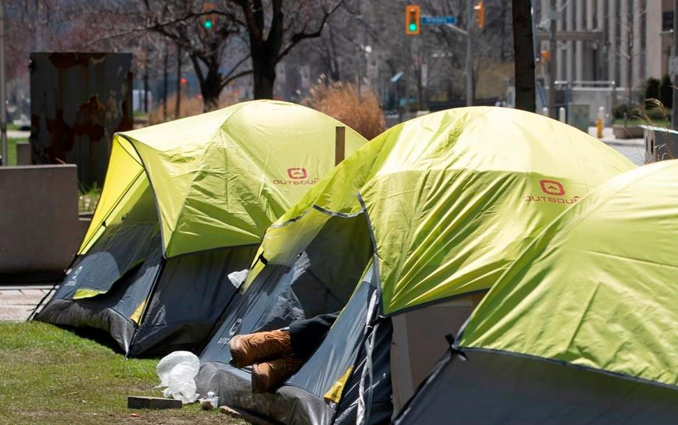 Una persona sin hogar yace en una tienda de campaña instalada en una reserva central en el centro de Toronto