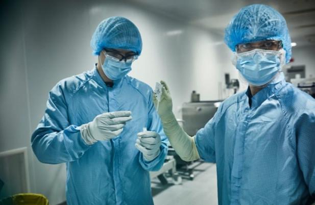 Los biotecnólogos de Oxford Biomedica revisan una muestra de la vacuna Oxford / AstraZeneca.