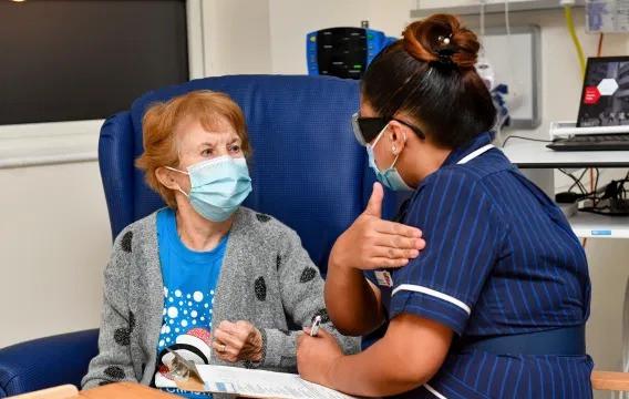 La enfermera May Parsons prepara a Margaret Keenan, de 90 años, la primera paciente del Reino Unido en recibir la vacuna Pfizer-BioNTech COVID-19, en el Hospital Universitario de Coventry, Inglaterra, el 8 de diciembre de 2020.