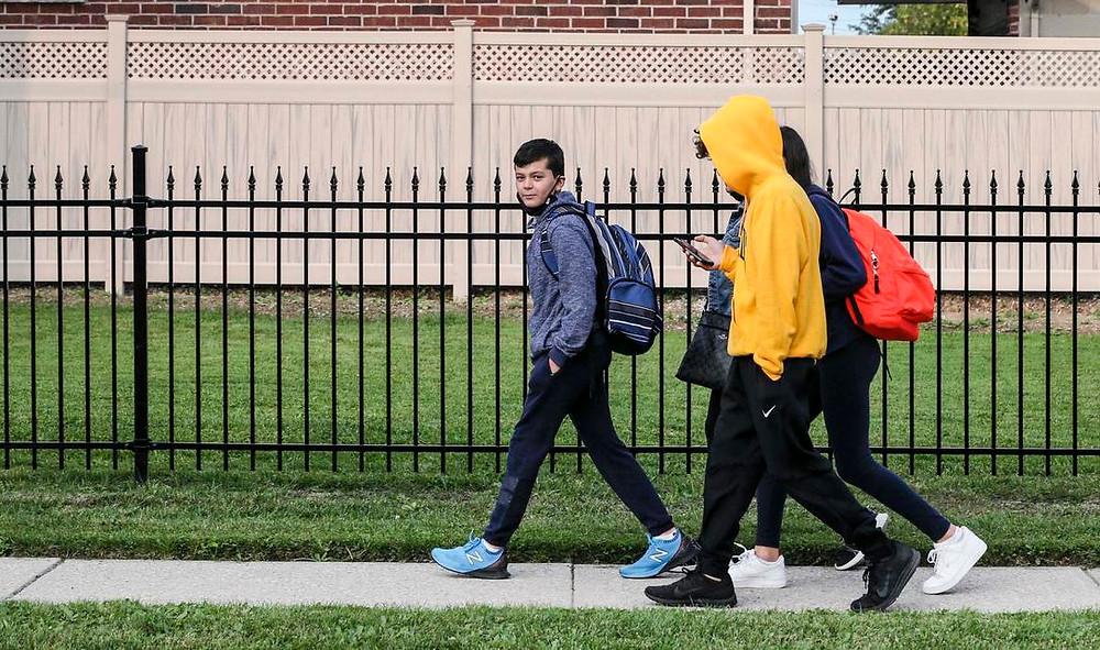 Michael Colonna, de 11 años, camina con su familia hasta el primer día del sexto grado en St. Norbert, parte del TCDSB