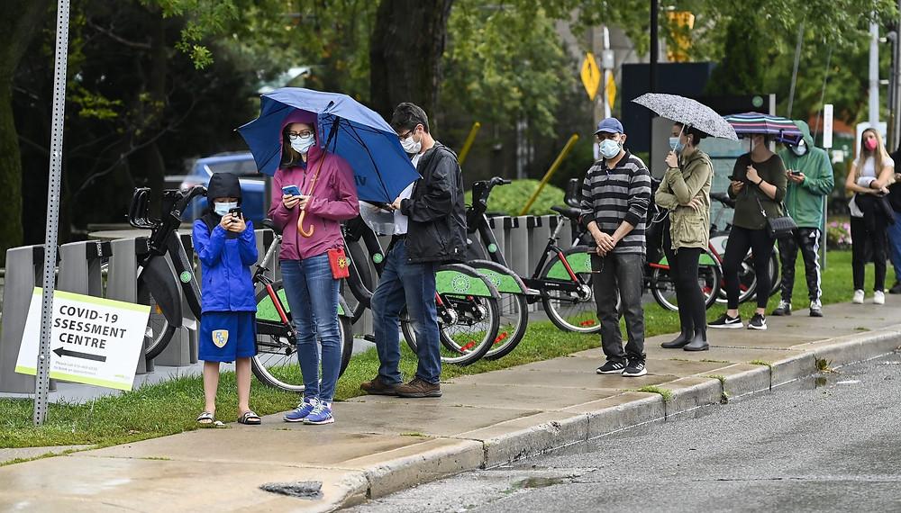 Las personas hacen fila para hacerse la prueba de COVID-19 en un centro de pruebas en Toronto
