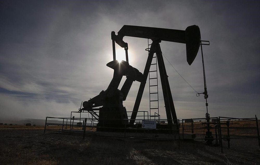 Un pumpjack trabaja en una boca de pozo en una instalación de petróleo y gas cerca de Cremona, Alta., Sábado 29 de octubre de 2016.