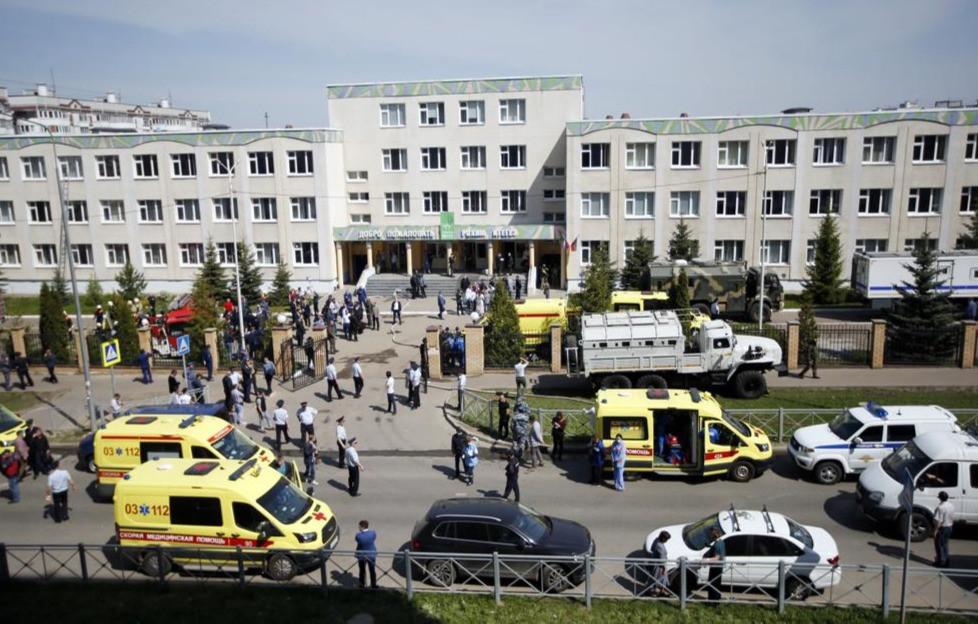 Ambulancias, patrullas de policía y un camión están estacionados en una escuela después de un tiroteo en Kazán, Rusia, el martes 11 de mayo de 2021.