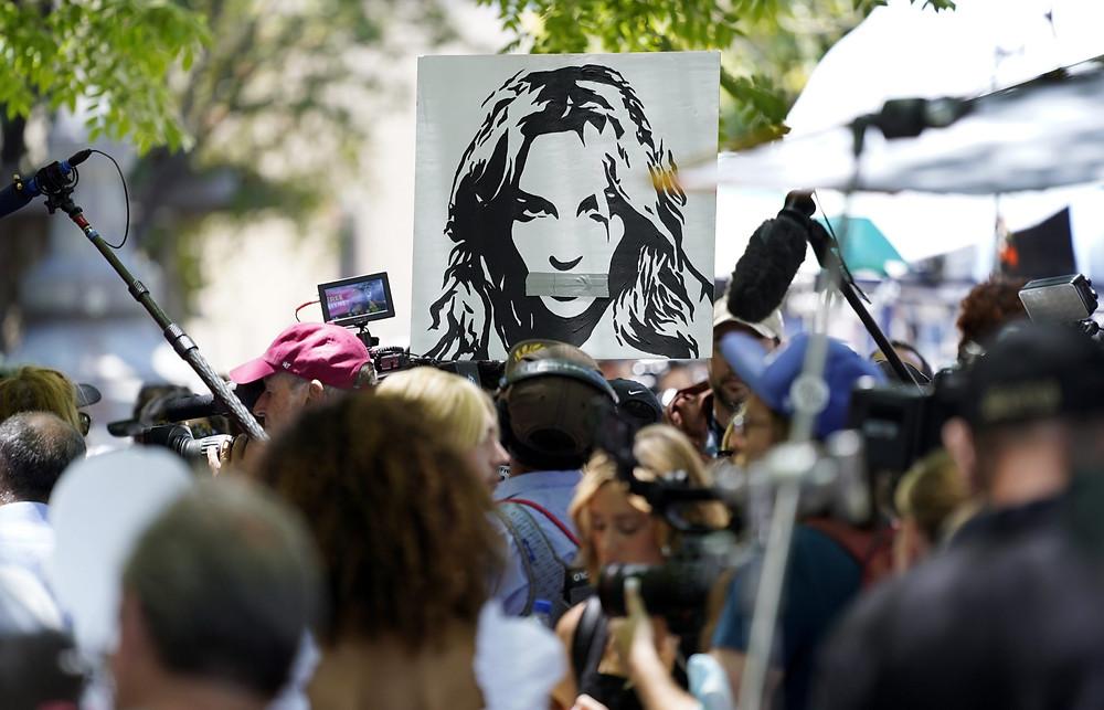 Un retrato de Britney Spears se cierne sobre simpatizantes y miembros de los medios fuera de una audiencia judicial sobre la tutela de la cantante pop en el Palacio de Justicia de Stanley Mosk, el miércoles 23 de junio de 2021, en Los Ángeles.