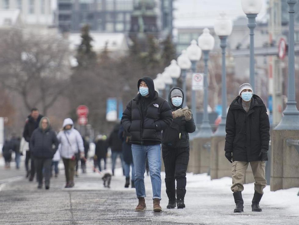 Las personas usan mascarillas mientras caminan por Old Port en Montreal, el viernes 1 de enero de 2021, mientras la pandemia de COVID-19 continúa en Canadá y en todo el mundo.