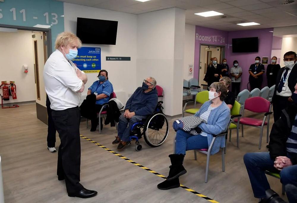 El primer ministro británico, Boris Johnson, se encuentra con personas que esperan su vacuna durante una visita a un centro de vacunación contra el coronavirus en el Centro de Salud y Bienestar en Orpington, sureste de Londres, el lunes.
