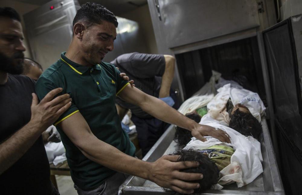 Un pariente palestino se lamenta frente a los cuerpos de cuatro hermanos jóvenes de la familia Al-tanani que fueron encontrados bajo los escombros de una casa destruida luego de los ataques aéreos israelíes en Beit Lahiya, en el norte de la Franja de Gaza, el viernes 14 de mayo de 2021.