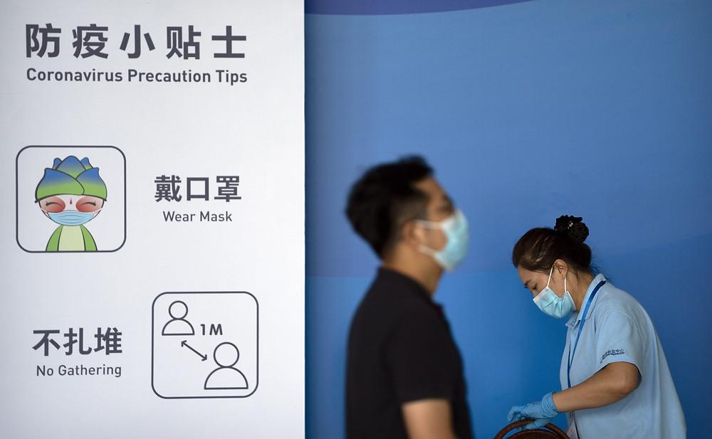 La gente pasa junto a un gráfico que recuerda a los visitantes que usen máscaras y practiquen el distanciamiento social para evitar la propagación del COVID-19 en la Feria Internacional de Comercio de Servicios de China (CIFTIS) en Beijing, el viernes 3 de septiembre de 2021.