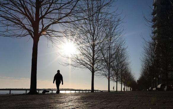 Unos peatones caminan por la orilla del lago al pie de la calle Sherbourne mientras el sol cuelga bajo en el cielo.