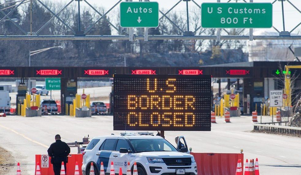 Los funcionarios de aduanas de EE. UU. Se paran junto a un letrero que dice que la frontera de EE. UU. Está cerrada en la frontera de EE. UU./ Canadá en Lansdowne, Ontario, el 22 de marzo de 2020.