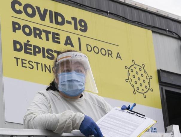 Un trabajador de salud espera a los pacientes en una clínica de prueba de COVID-19 en Montreal, el viernes 11 de diciembre de 2020.