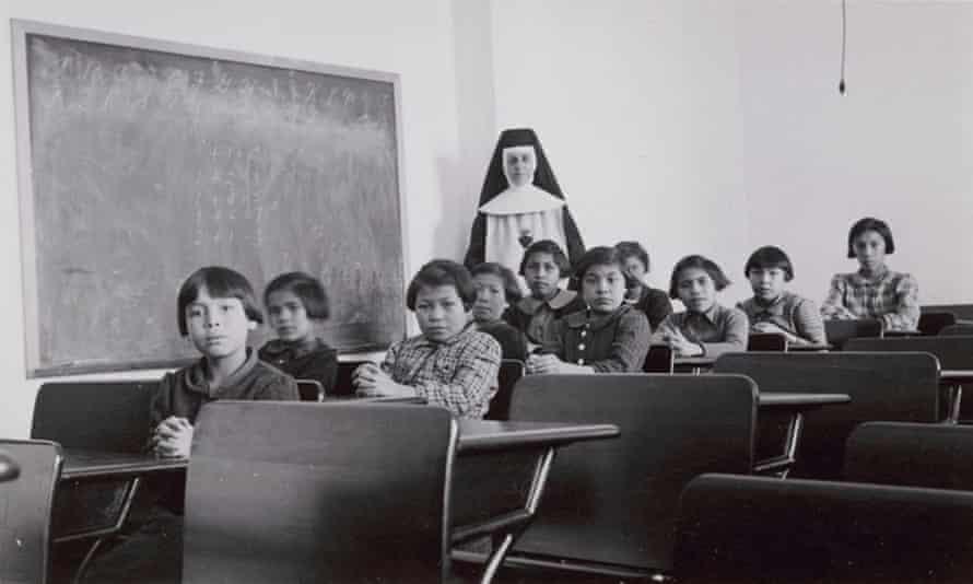 Un grupo de alumnas y una monja posan en un aula de la escuela residencial Cross Lake Indian en Cross Lake, Manitoba, en febrero de 1940.