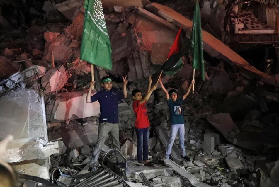 Niños palestinos ondean las banderas verdes de Hamas y sus banderas nacionales parados sobre los escombros de un edificio destruido mientras celebran el acuerdo de alto el fuego entre Israel y Hamas en la ciudad de Gaza, la madrugada del viernes 21 de mayo de 2021.