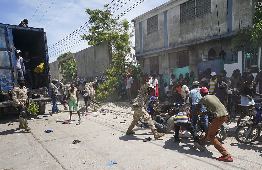 La policía confronta a los residentes que alcanzaron temporalmente un camión cargado con suministros de socorro, en Les Cayes, Haití, el viernes 20 de agosto de 2021.