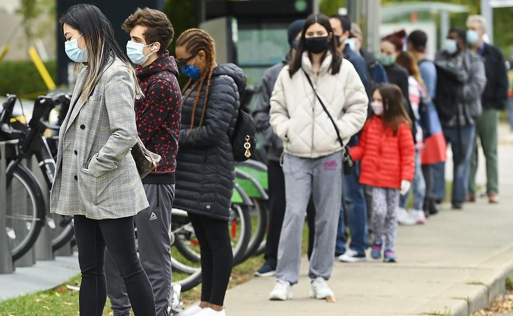 Las personas hacen fila en un centro de evaluación de COVID-19 con cita previa solo en el Hospital Michael Garron durante la pandemia de COVID-19 en Toronto el jueves 8 de octubre de 2020.