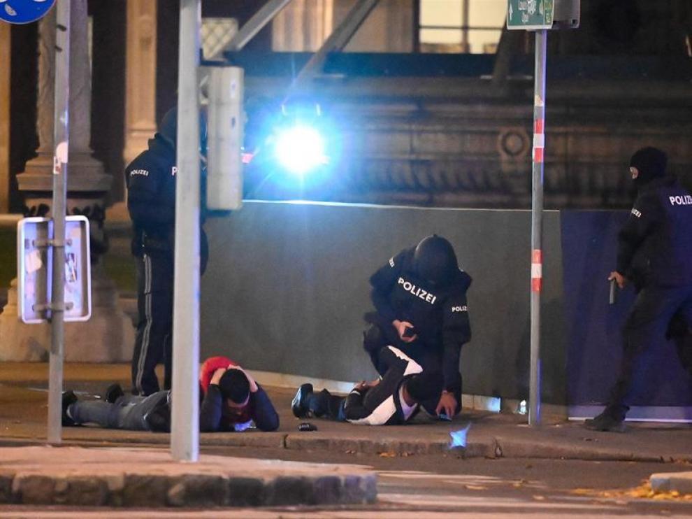 La policía de Viena cachea a dos individuos tras los ataques terroristas en la capital austriaca.