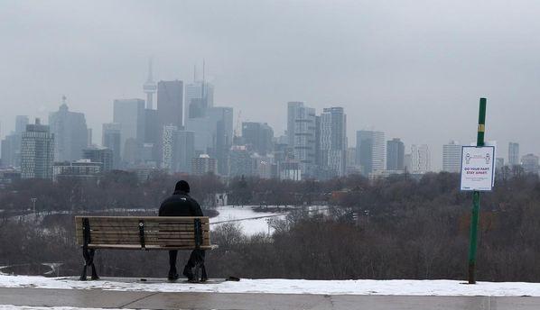 Un hombre se sienta en un banco en Riverdale Park East mientras Ontario enfrenta restricciones más estrictas para frenar la propagación de la pandemia de COVID-19 en Toronto.