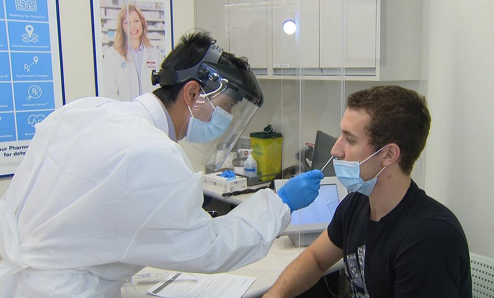 Un hombre recibe una prueba de frotis nasal de COVID-19 en un Shopper's Drug Mart en Toronto.