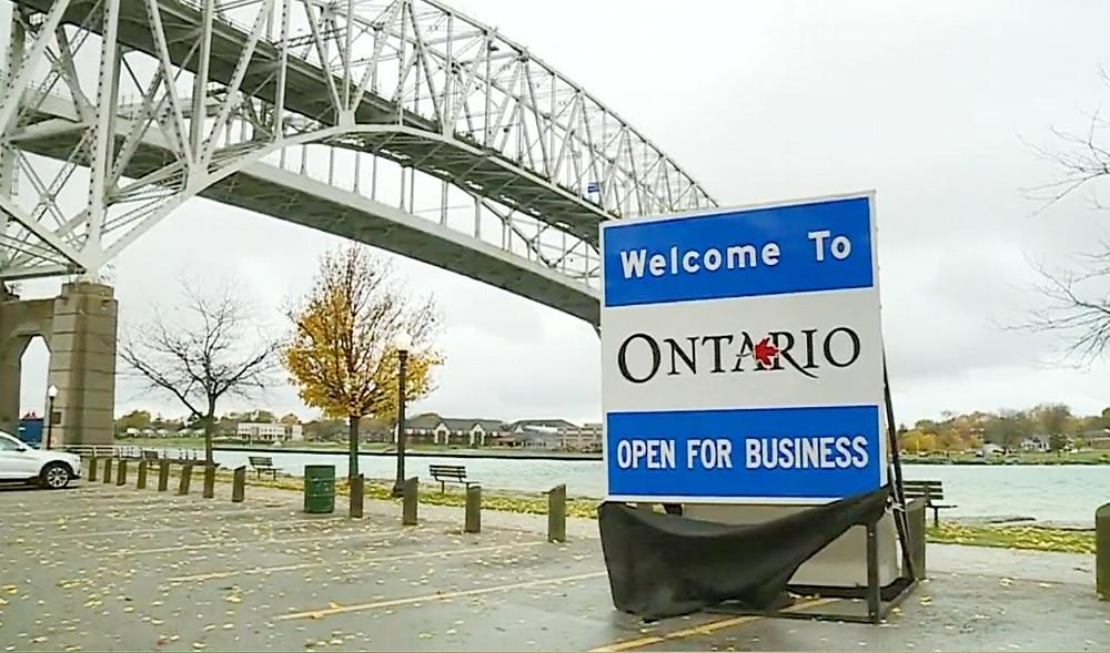 """Un letrero que dice """"Bienvenido a Ontario: Abierto para negocios"""" se ve en el cruce fronterizo de EE. UU. En Point Edward, Ontario, el 2 de noviembre de 2018."""