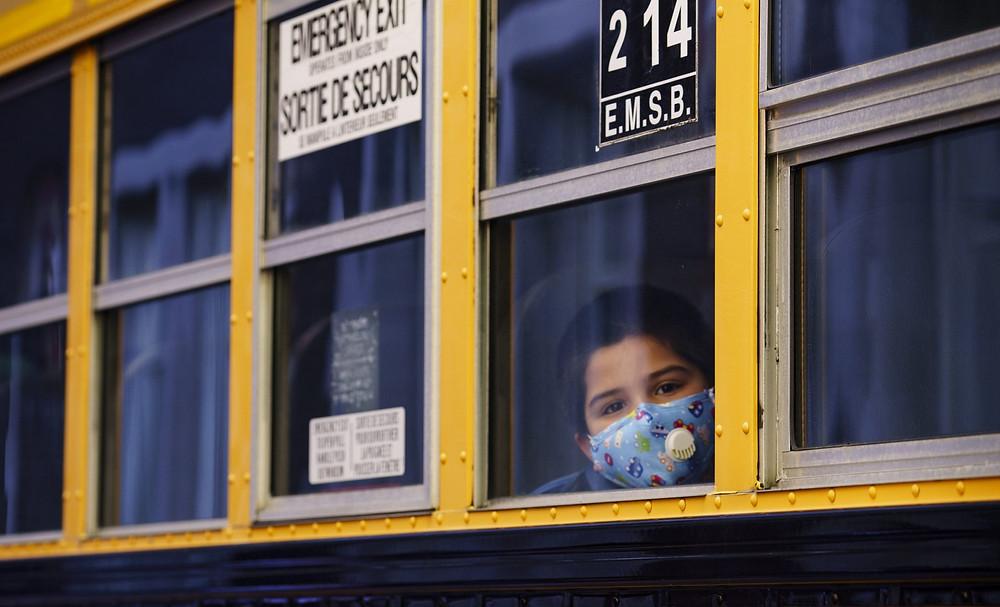 Un estudiante mira a través de la ventana de un autobús escolar cuando llega a la escuela primaria Bancroft en Montreal, el 31 de agosto de 2020.