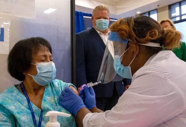 El premier Doug Ford observa cómo la segunda dosis de la vacuna Pfizer-BioNTech COVID-19 en Canadá se administra a la trabajadora de apoyo personal Anita Quidangen por la enfermera registrada Hiwot Arfaso en el Instituto Michener en Toronto el lunes.