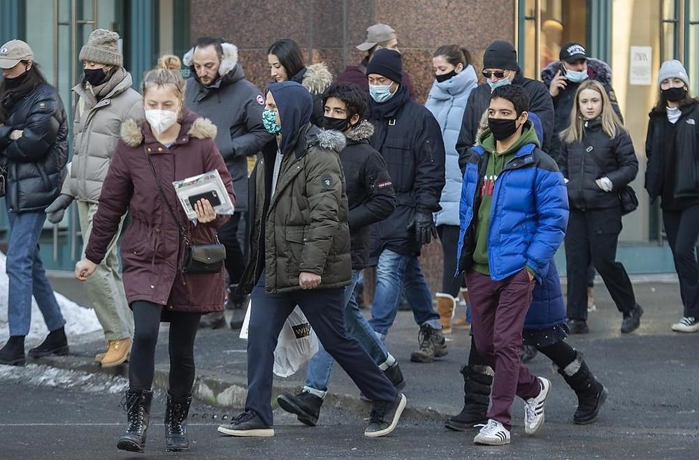 Las personas usan mascarillas cuando cruzan una calle en Montreal, el domingo 14 de febrero de 2021, mientras la pandemia de COVID-19 continúa en Canadá y en todo el mundo.