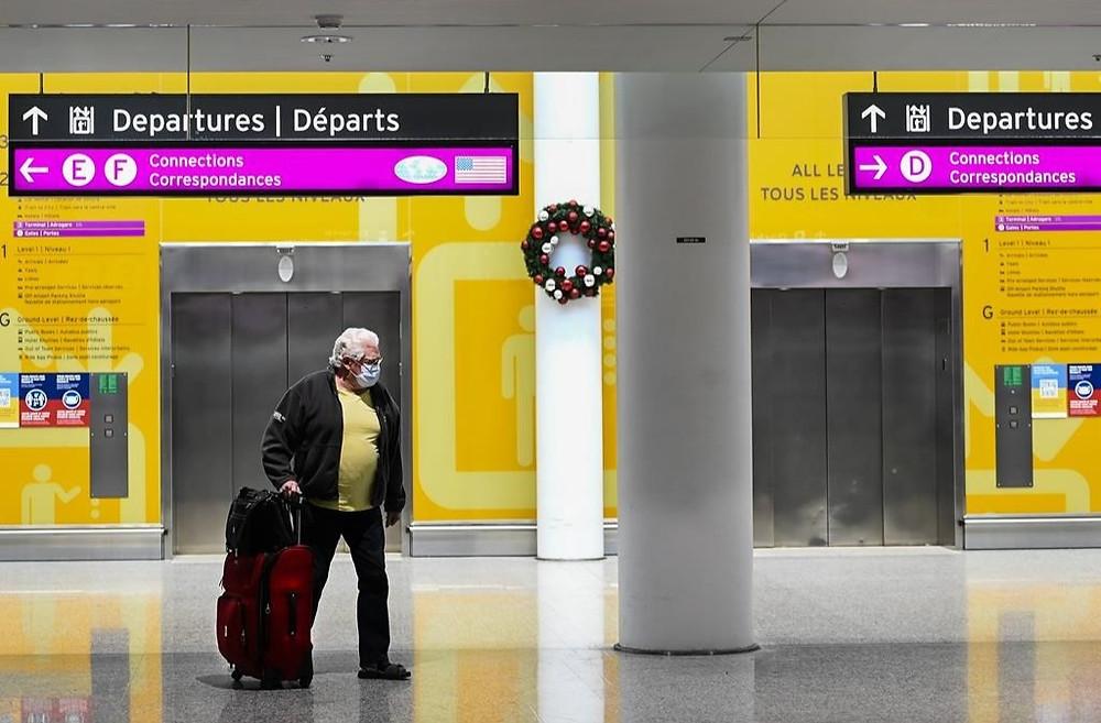 Un hombre atraviesa el Aeropuerto Internacional Pearson durante la pandemia de COVID-19 en Toronto el lunes 14 de diciembre de 2020. Los viajeros internacionales ahora tendrán que pagar una prueba de COVID-19 si es necesario.