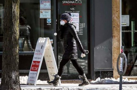 Una mujer camina en el centro de Toronto, 3 de febrero de 2021.
