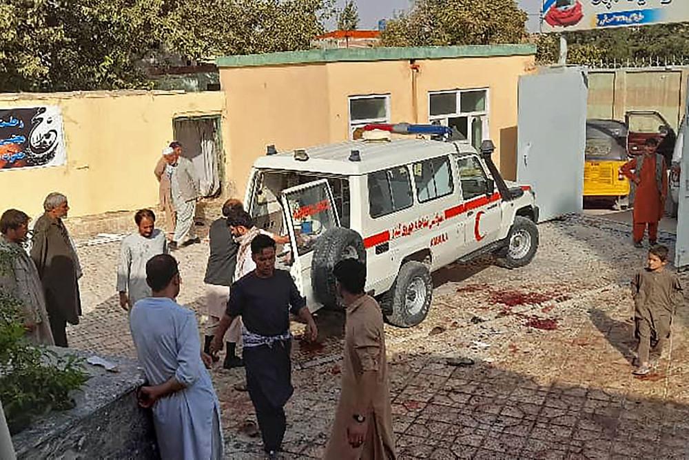 Hombres afganos junto a una ambulancia después de un ataque con una bomba en una mezquita en Kunduz el 8 de octubre de 2021.