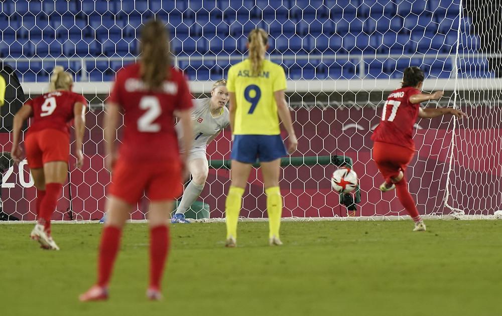 La canadiense Jessie Fleming anota en un tiro penal que supera a la portera sueco Hedvig Lindahl durante el juego por la medalla de oro en fútbol femenino en los Juegos Olímpicos de Tokio en Yokohama, Japón, el viernes 6 de agosto de 2021.