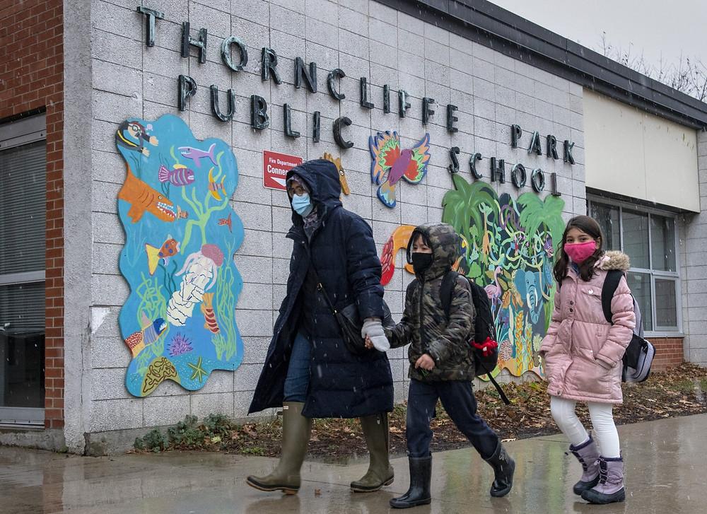 Una familia pasa junto al letrero en la escuela pública Thorncliffe Park en Toronto el viernes 4 de diciembre de 2020. Toronto Public Health cerró la escuela debido a un brote de COVID19.