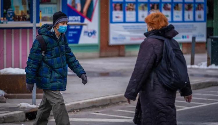 Se ve a peatones enmascarados con ropa de invierno cruzando las calles en Ottawa mientras la provincia confirma 1.958 nuevos casos de COVID-19 y 43 muertes.