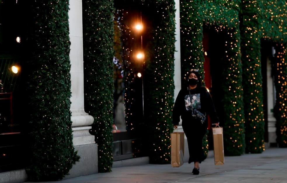 Una mujer pasa junto a las decoraciones navideñas en Oxford Street durante un segundo encierro en Londres, el jueves 19 de noviembre de 2020.